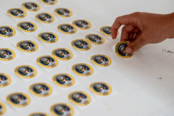 """Hand selecting an """"I voted"""" sticker from a sheet of stickers"""